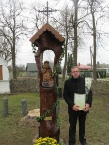 Marijus Macis su vyskupo padėka rankose prie dovanoto parapijai Rūpintojėlio